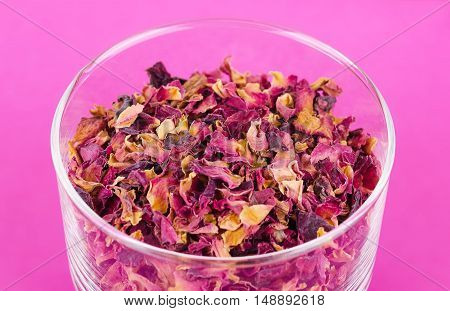 Rose petals in a glass bowl over pink. Dried blossoms, used for perfumes, cosmetics, teas and baths. Purple and orange colored organic herb. Isolated macro photo close up from above.