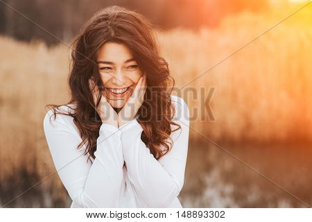 beautiful sunny portrait of a girl wearing white clothes. Face laughing woman outdoors with copy space