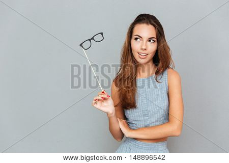 Pensive young woman with glasses props standing and thinking over grey background