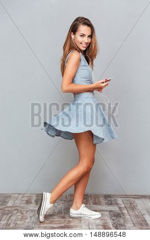 Full length of cheerful young woman listening to music from mobile phone over grey background