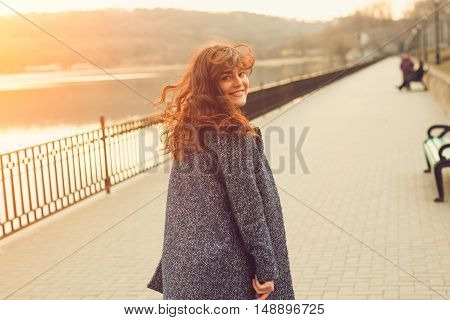Happy overweight woman walking the city street by the lake. Dynamic portrait of girl with wind on hair at sunset with sun flare effect