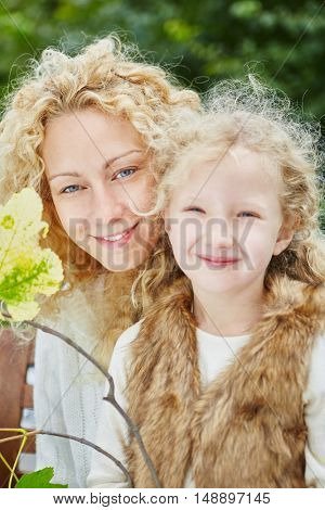 Mother and daugther with blond curly hair happily looking in the camera and smiling