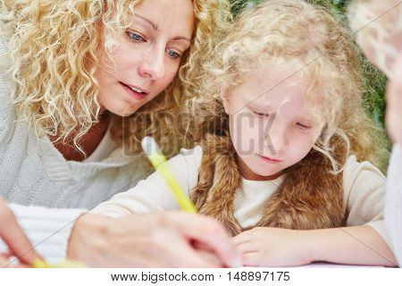 Gril drawing and learning with educator in kindergarten