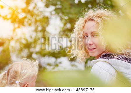 Single mother and her daugther in autumn at park