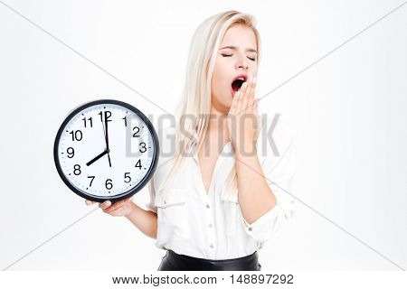Tired businesswoman yawning and holding clock isolated on a white background
