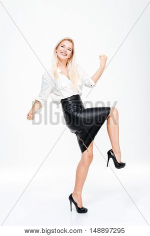 Full length of funny excited young businesswoman celebrating success over white background