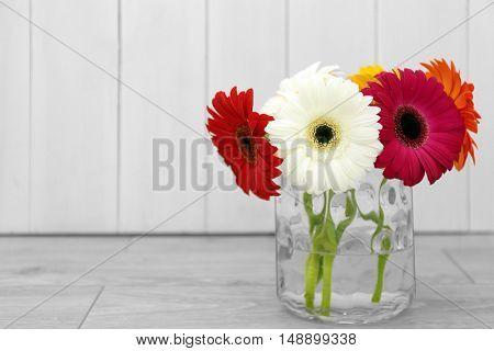 Beautiful gerbera flowers in vase on blurred wooden background
