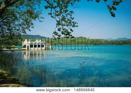 View of a stunning old boathouse on a beautiful blue lake surrounded by green hills on a quiet clear day