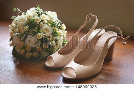 Wedding shoes and bouquet of white roses on the floor