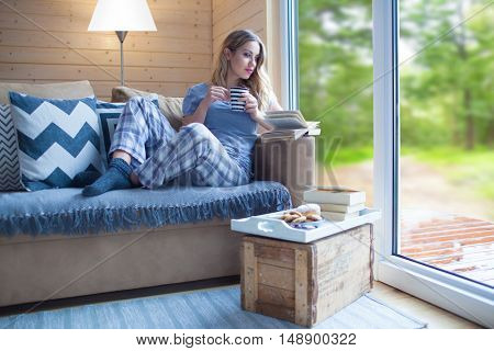 Young beautiful blonde woman with cup of coffee and book sitting home by the window. Summer spring green woods view. Lazy day off concept