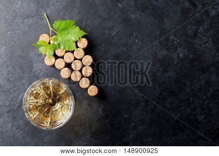 Wine corks grape shape, white wine glass and vine on stone table. Top view with copy space for your text