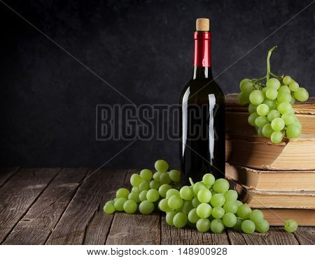 Red wine and white grapes on table in front of stone wall with copy space
