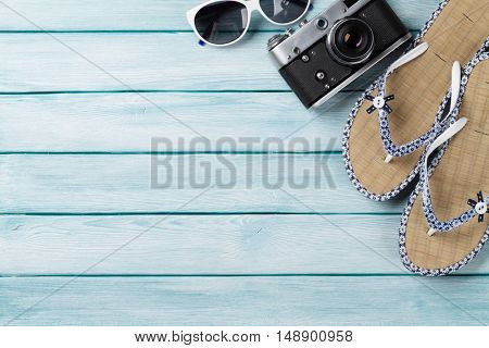 Beach accessories. Flip flops, camera and sunglasses on wooden background. Top view with copy space