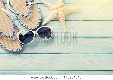 Beach accessories. Flip flops, sunglasses and starfish on wooden background. Top view with copy space. With sunny toned