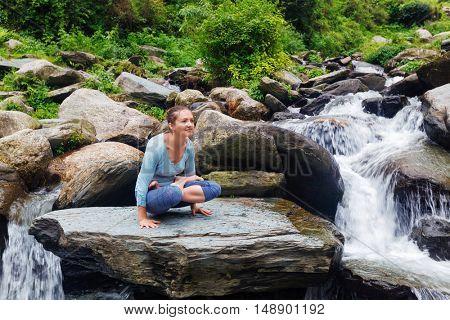 Yoga exercise outdoors -  woman doing Ashtanga Vinyasa Yoga arm balance strength training asana Tolasana - scales pose at waterfall in Himalayas