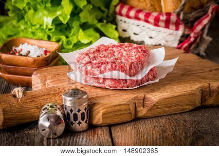 Ingredients for making homemade burger on wooden cutting board