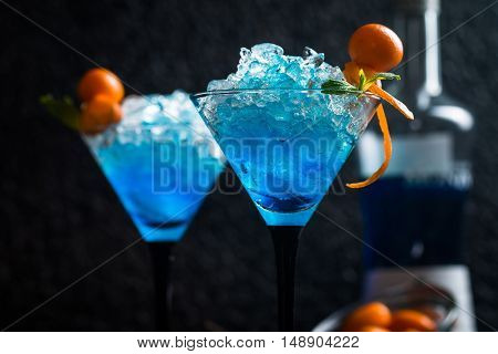 Blue cocktail in martini glasses with ice and Kumquat on black background