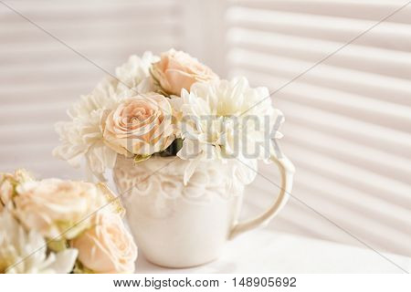Bouquet of beautiful roses in a cup on a  table