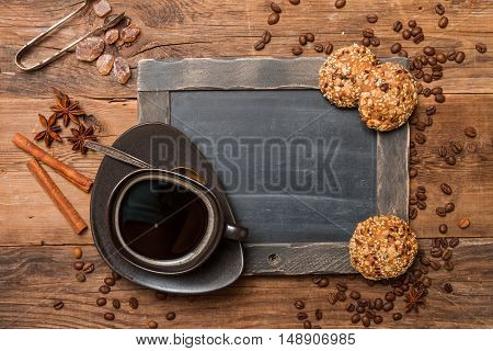 Cup of coffee and chalk board menu on wooden vintage background, top view