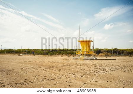 Clouds and blue sky above an empty sandy beach and a yellow lifeguard tower