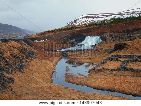 Icelandic Waterfall Fossarrett in Volcanic landscape with snow mountains in the background