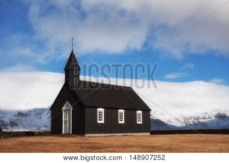Black Church of Budir in Iceland at daytime with blue sky and clouds