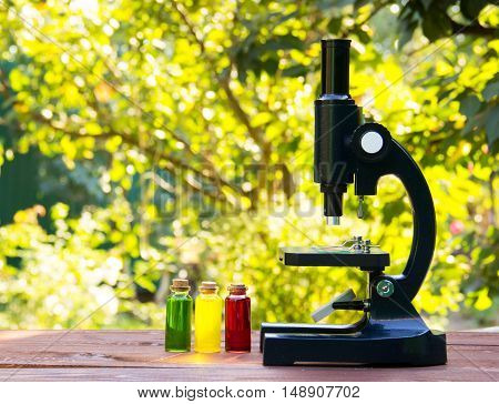 Microscope and glass flasks with colored liquids on a wooden table. An optical device for a student. School concept. Copy space