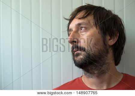 Profile portrait od sad and disappointed man with unshaven beard looking toward the light coming from room window