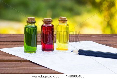 Three glass vials and blank for records on a wooden table. Chemical experiments. School concept. Household experiences
