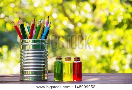Colored pencils in a tin can and bottles with colored liquids on a wooden table. Natural green background. Green blur. Copy space. School concept.