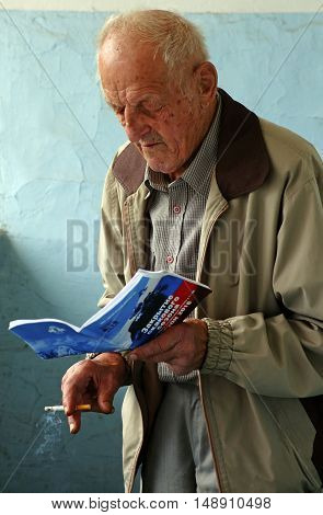 PYATIGORSK, RUSSIA - SEPTEMBER 25,2016: Portrait old fan watching the race schedule the closing day of the racing season,hippodrome in Pyatigorsk,Caucasus,Russia on September 252016.