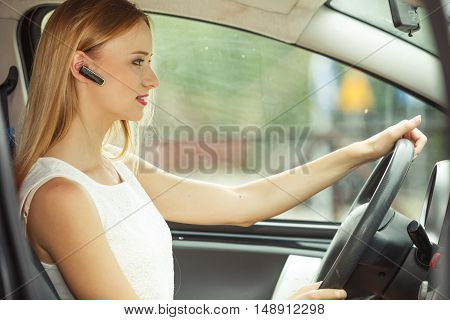 Transport and safety concept. Young blonde woman driving car using her mobile phone and headset side view
