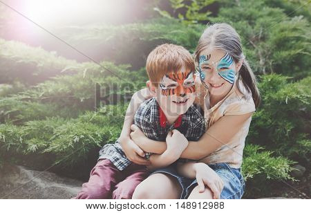 Happy children with face art paint in park. Boy and girl outdoors on child birthday masquerade party have fun, laugh and hug each other as friends or siblings. Entertainment and holidays.