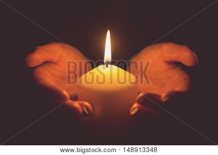Vintage tone of hands holding a burning candle in dark