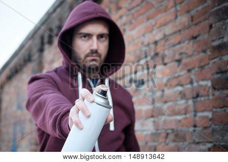Hooded Tagger Writing Graffiti On Urban Walls