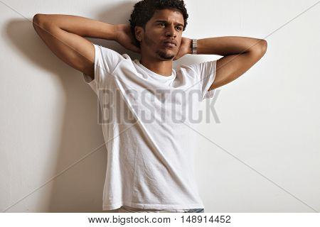 Thoughtful and dreamy handsome young man in white plain t-shirt with hands behind his head against a blank white wall
