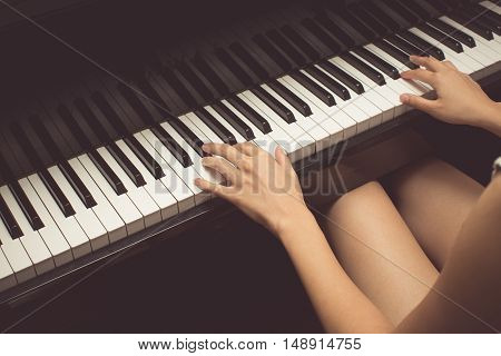 Vintage tone of women playing a piano