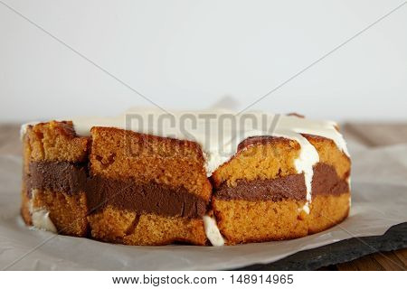 Close up shot of a moist fresh cake with cream and chocolate lying on a piece of parchment paper