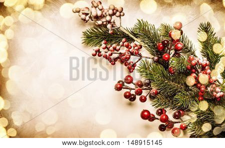 Christmas  decoration background: fir branches and holly berries on light background, in vintage style