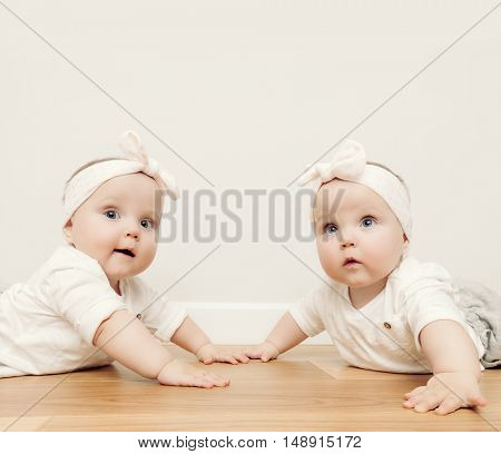 Cute baby twin sisters crawl together on wooden floor wearing funny headbands. Vintage