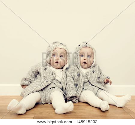 Cute baby twins sitting on wooden floor and wearing warm cozy sweaters. Curious face expression. Vintage