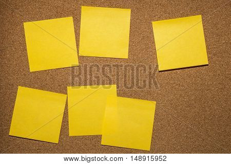 five yellow reminder sticky note on cork board