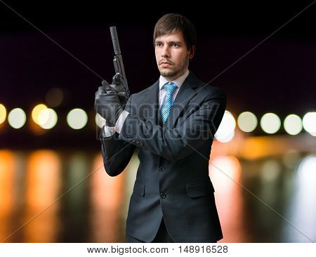 Killer Or Assassin Holds Pistol With Silencer In Hands At Night.