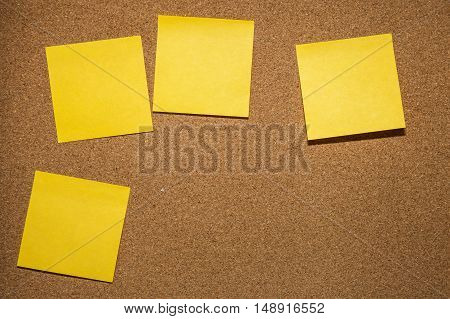 four yellow reminder sticky note on cork board