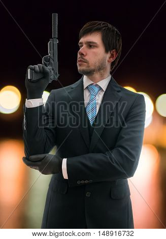 Secret Agent In Suit Holds Pistol With Silencer In Hand At Night