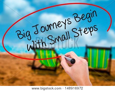 Man Hand Writing Big Journeys Begin With Small Steps  With Black Marker On Visual Screen