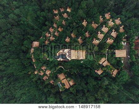 Aerial view of luxury resort in rain forest surrounded by trees. Hotel with cottages and swimming pool.