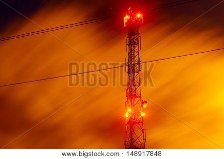 communications tower antenna night photo with a long exposure. yellow orange night sky version