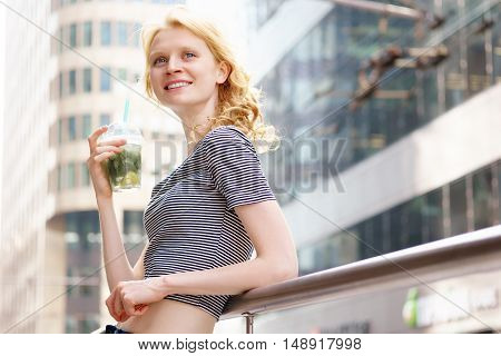 Young slim hipster woman walking and drinking mojitos, portrait on urban background on sunny hot day