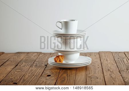 Similar but different white t-cups perched on top of each other with a tiny bit of light brown sponge cake on a saucer